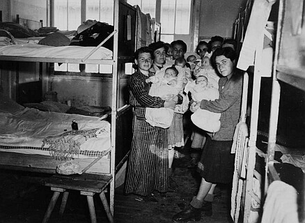 This photo was made by U.S. soldiers after the liberation of the Dachau concentration camp on 29 April 1945. Amidst the death, they met seven Jewish women with their babies. Marika Nováková, the baby on the front left arm, his mother Eva Fleischmanová. The second baby of the right is Leslie Rosenthal. [Foto: WDR / USHMM]