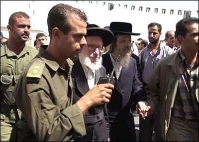 FILE - Guard escort Rabbi Moshe Hirsch, center, before a meeting with Arafat in the West Bank town of Ramallah, Tuesday, Sept. 16, 2003.