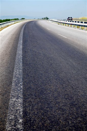 """The crushed remains of thousands of tiny frogs stain the Egnatia highway in northern Greece, after the tarmac was covered by a horde of small amphibians on Wednesday, May 26, 2010. Officials closed the key northern highway near the town of Langadas for two hours after what police called """"a carpet of frogs"""" covered the road. Police said the amphibians probably left a nearby lake to look for food. (AP Photo/Aggelioforos, Pavlos Makridis)"""