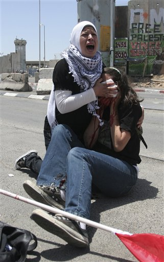 A Palestinian woman reacts as she holds a cloth to the bleeding face of an American activist who was wounded during clashes with Israeli troops at the Kalandia checkpoint between the West Bank city of Ramallah and Jerusalem, Monday, May 31, 2010.  The clashes erupted during a protest against Israeli naval commandos on Monday storming a Gaza-bound flotilla of ships, that left at least 10 passengers dead, and dozens of activists and at least 10 Israeli soldiers wounded. (AP Photo/Majdi Mohammed)