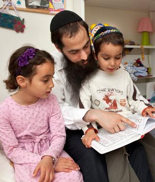 Lone Rabbi: Shneur Kesselman, reading to his children, insists he won't leave despite the dangers.