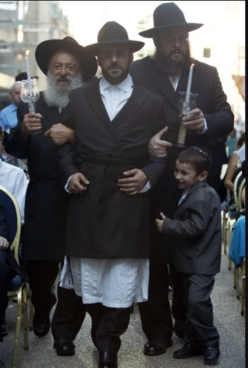 The Groom Yossi Schlass, Center, of Jerusalem, walking down to the Chupah in a Hasidic Jewish ceremony Monday in the Peace Plaza.