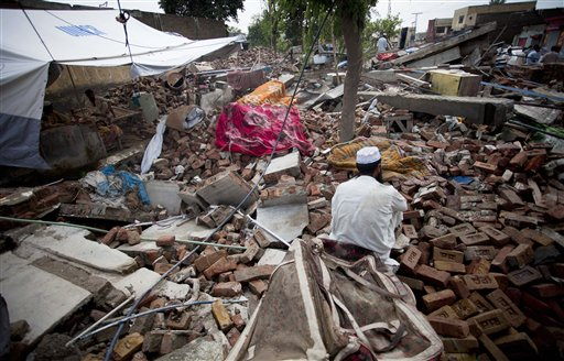 A flood-affected man sits over debris of his house collapsed by flooding in Nowshera, northwest Pakistan, Monday, Aug. 9, 2010. The number of people suffering from the massive floods in Pakistan exceeds 13 million, more than the combined total of the 2004 Indian Ocean tsunami, the 2005 Kashmir earthquake and the 2010 Haiti earthquake, the United Nations said Monday. (AP Photo/B.K. Bangash)