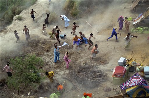 Pakistani villagers chase to relief supplies dropped from an army helicopter in a heavy flood-hit area of Mithan Kot, in central Pakistan. The government has struggled to cope with the scale of the disaster, which has killed at least 1,500 people, prompting the international community to help by donating tens of millions of dollars and providing relief supplies. (AP Photo/Khalid Tanveer)