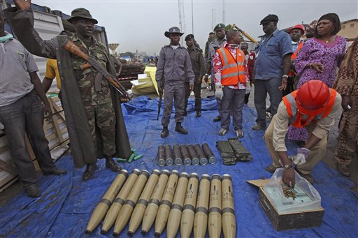 A Nigerian soldier, right, gestures as he and others show journalist arms at Lagos, Nigeria, Wednesday, Oct. 27, 2010. Artillery rockets like those often used by insurgents in Afghanistan were inside an illegal arms shipment seized by authorities in Nigeria. Authorities showed the weaponry to journalists Wednesday at Lagos' busy Apapa Port. (AP Photo/Sunday Alamba)