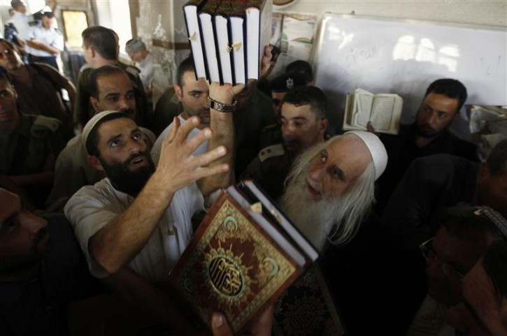 Rabbi and peace activist Menachem Froman (R) watches as Korans are given to Palestinians at a mosque after Monday's attack in the West Bank village of Beit Fajjar near Bethlehem October 5, 2010. Jewish settlers on Tuesday gave Korans to Palestinians in the West Bank village whose mosque was burned in an attack blamed on militants in the settler movement. REUTERS/Ammar Awad
