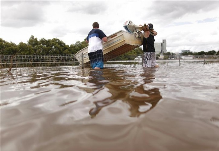 Two men lift their boat over a fence as they travel through flooded streets, in a commercial area of Brisbane January 13, 2011. Flood water in Australia's third-biggest city of Brisbane peaked below feared catastrophic levels on Thursday. With 35 suburbs flooded, many parts of Brisbane looked more like Venice as residents used boats to move about flooded streets, where traffic signs peeped above the stagnant water.  REUTERS/Tim Wimborne