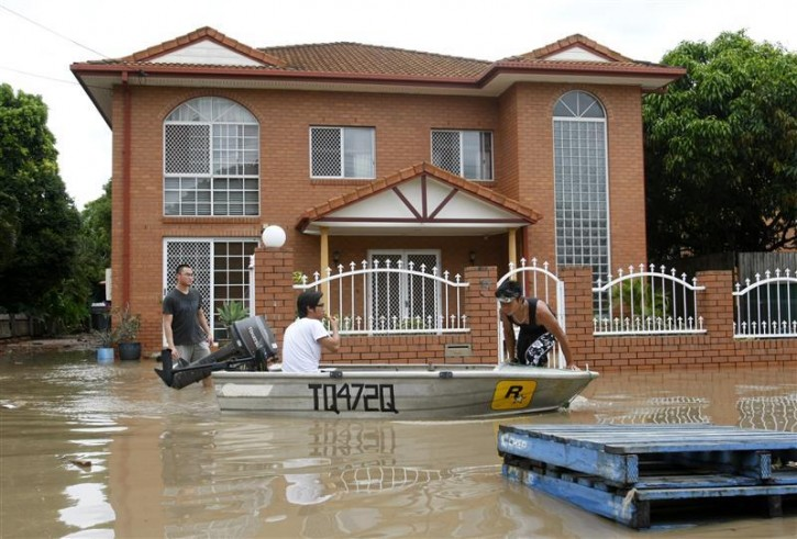 Residents paddle past a flooded house in the Brisbane suburb of Saint Lucia January 13, 2011. Flood water in Australia's third-biggest city peaked below feared catastrophic levels on Thursday but Brisbane and other devastated regions faced years of rebuilding and even the threat of fresh floods in the weeks ahead.   REUTERS/Mick Tsikas