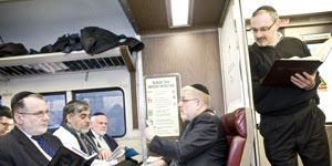 Rabbi Pesach Lerner (fourth from left) leads a class in the Talmud on the LIRR, making getting to work more stimulating for commuters.Photo: Allison Joyce