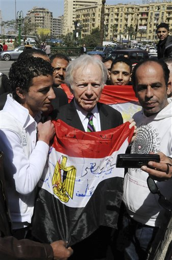 Egyptians hold their national flag as they have their photo taken with U.S. senator Joseph Lieberman, I-CT, center, during his visit to Tahrir Square, the focal point of the Egyptian uprising, in Cairo, Egypt, Sunday, Feb. 27, 2011. (AP Photo/Mohammed Ismail)