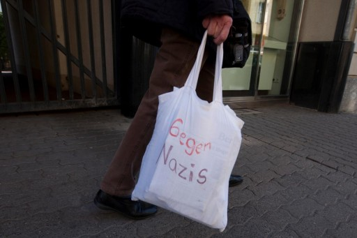 """Picture taken Thursday March 24, 2011 showing Irmela Mensah-Schramm (65) from Berlin carrying a bag with the inscription """"Against Nazis' on a street in Berlin's Schoeneweide district. For about the last 25 years Irmela Mensah-Schramm has walked through the streets of Berlin and other cities to paint over or remove paintings, stickers or slogans from neo-nazis from walls, street lamps and other places. (AP Photo/Markus Schreiber)"""