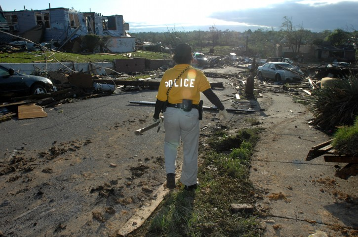 A police officer surveys storm damage in Pratt City, Alabama, USA, 28 April 2011. Severe weather and more than 100 tornados destroyed towns and killed more than 200 people across the southern USA on 27 April 2011.  EPA/CHRISTINE PRICHARD