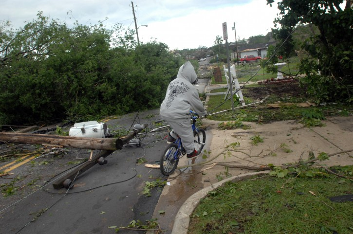 A person on a bicycle maneuvers around debris after homes and businesses were hit by strong storms and tornados in Pratt City, Alabama, USA, 28 April 2011. Severe weather and more than 100 tornados destroyed towns and killed more than 200 people across the southern USA on 27 April 2011.  EPA/CHRISTINE PRICHARD