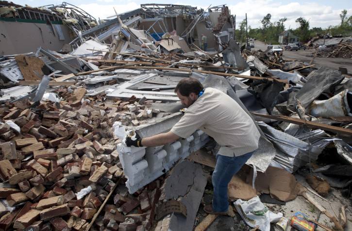 Heath Meherg helps clean up his destroyed business in Cullman, Ala., Thursday, April 28, 2011. A swarm of tornadoes killed dozens of people across the state. (AP Photo/Dave Martin)