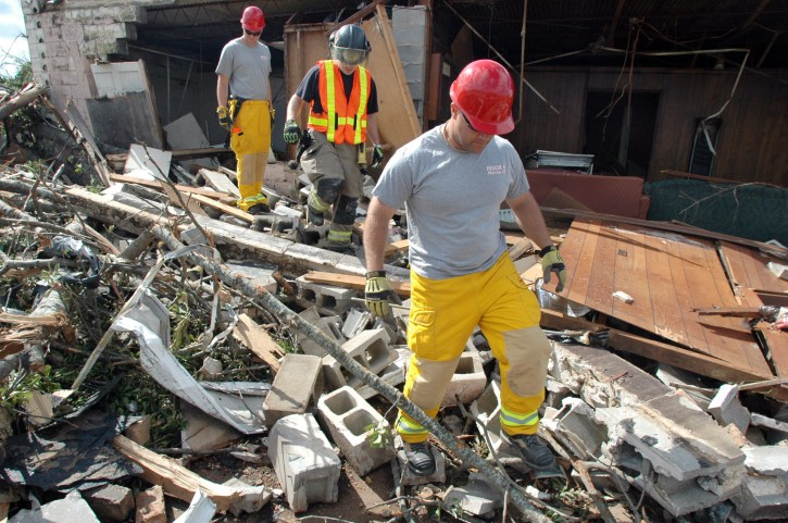 Firefighters search the rubble of a home in the Alberta City section of Tuscaloosa, Ala., on Thursday, April 29, 2011. Dozens of tornadoes ripped through the South, flattening homes and businesses and killing at least 215 people in six states in the deadliest outbreak in nearly 40 years. (AP Photo/Jay Reeves)