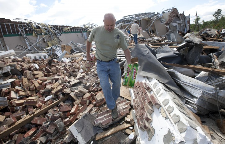 Greg Arndt carries belongings from a destroyed business in Cullman, Ala., Thursday, April 28, 2011, after tornadoes ripped through the area. (AP Photo/Dave Martin)