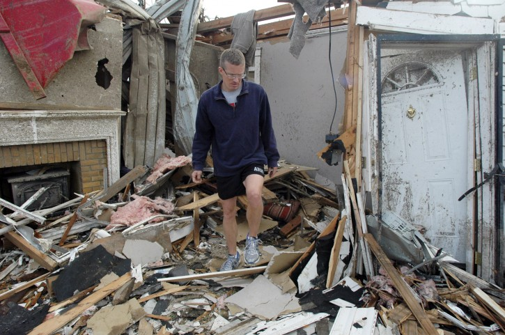 John Boxmeyer climbs through the rubble of a home where he was helping friends recover belongings on Thursday, April 28, 2011, in Tuscaloosa, Ala. The storm demolished a neighborhood near the University of Alabama campus. (AP Photo/Jay Reeves)