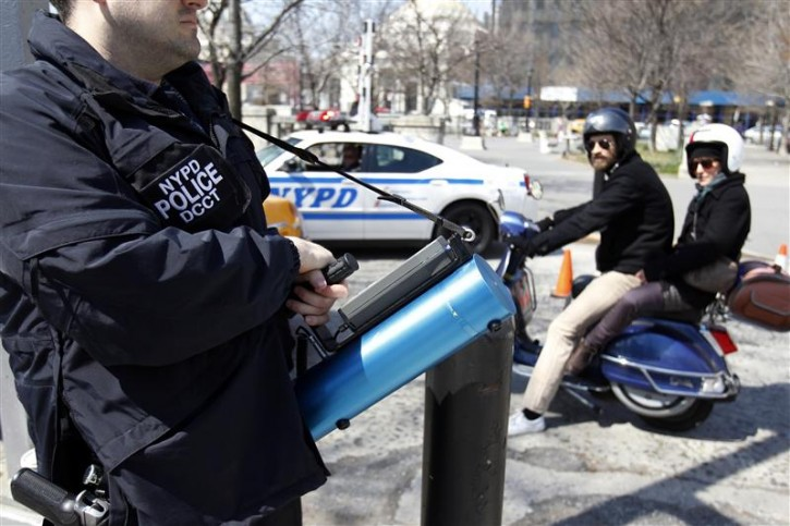 """A member of the NYPD holds a device used to detect levels of radiation as motorists pass by during a multi-agency """"dirty bomb"""" exercise led by the New York Police Department in the Brooklyn section of New York April 9, 2011.  REUTERS/Jessica Rinaldi"""