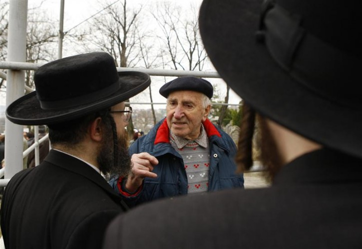 Pogrom survivor Leizer Finkelstein (C) talks to Rabbis from England and the United States after a burial ceremony of the remains of dozens of Jews in a cemetery in Iasi, 410 km (251 miles) north of Bucharest, April 4, 2011. Romania's Jewish community buried on Monday the remains of dozens of Jews killed by Romanian troops during World War Two and found in a mass grave in the north of the country. The memorial, dedicated to about 60 victims unearthed in a forest area near the village of Popricani, took place in the Jewish cemetery of Iasi in northeastern Romania. Archaeologists unearthed the mass grave in November 2010. REUTERS/Bogdan Cristel
