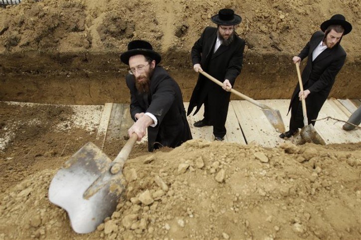 Rabbis from England and the United States bury the remains of dozens of Jews in a cemetery in Iasi, 410 km (251 miles) north of Bucharest, April 4, 2011. Romania's Jewish community buried on Monday the remains of dozens of Jews killed by Romanian troops during World War Two and found in a mass grave in the north of the country. The memorial, dedicated to about 60 victims unearthed in a forest area near the village of Popricani, took place in the Jewish cemetery of Iasi in northeastern Romania. Archaeologists unearthed the mass grave in November 2010. REUTERS/Bogdan Cristel