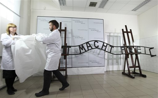 """Officials show the restored notorious """"Arbeit Macht Frei"""" (Work Sets You Free) sign in Oswiecim, Poland on Wednesday, May 18, 2011. The sign was stolen from the former Nazi death camp of Auschwitz in 2009 and bent and cut into several pieces. In painstaking conservation work it has been welded together. It has been replaced by a replica and the original will probably be moved to an exhibition hall at the camp's memorial. (AP Photo/ Jarek Praszkiewicz)"""