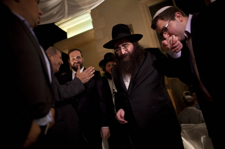 In this Monday, July 11, 2011 photo, a man kisses the hand of Rabbi Yoshiyahu Pinto, center, as he attends a wedding in Lod, central Israel. People, including some of Israel's wealthiest and most powerful, come seeking Pinto's blessing or his counsel on their business deals and personal lives. The veneration and consulting of miracle rabbis has a long history in Judaism, existing uncomfortably alongside a deeply rooted rationalist tradition. (AP Photo/Oded Balilty)