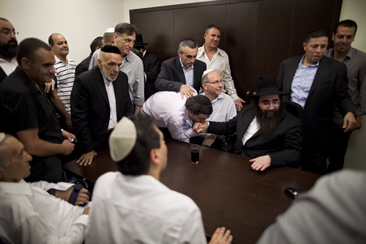 In this July 11, 2011 photo, followers surround Rabbi Yoshiyahu Pinto, center right, during a wedding in Lod, central Israel. People, including some of Israel's wealthiest and most powerful, come seeking Pinto's blessing or his counsel on their business deals and personal lives. The veneration and consulting of miracle rabbis has a long history in Judaism, existing uncomfortably alongside a deeply rooted rationalist tradition. (AP Photo/Oded Balilty)