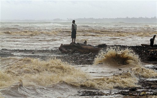 A resident watches the sea surge along a beach covered by debris after the passing of Hurricane Irene in Nagua on the northern coast of the Dominican Republic, Tuesday, Aug. 23, 2011. Irene was still lashing the northern coasts of Haiti and the Dominican Republic, where crews have begun cleaning up debris and the government warned of flooding. It was forecast to pass over or near the Turks and Caicos Islands and the southeastern Bahamas by Tuesday night and be near the central Bahamas early Wednesday. (AP Photo/Roberto Guzman)