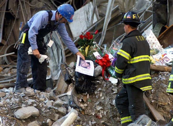 A New York City firefighter places a photograph amidst a pile of flowers and mementos from family members of the victims of the World Trade Center disaster amidst the wreckage of the World Trade Center following a memorial service for the victims of the September 11 attack at the site in New York, October 28, 2001.