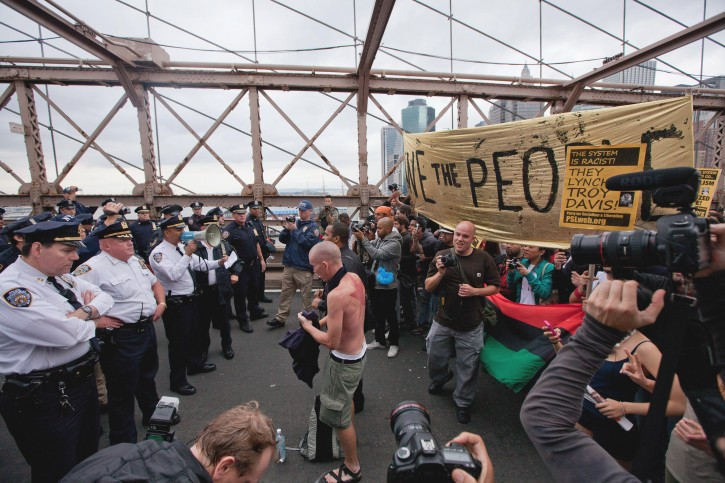 A police officer with a bullhorn addresses a  large group of protesters affiliated with the Occupy Wall Street movement who attempted to cross the Brooklyn Bridge, effectively shutting parts of the roadway down, Saturday, Oct. 1, 2011 in New York. Police arrested dozens while trying to clear the road and reopen for traffic.(AP Photo/Will Stevens)