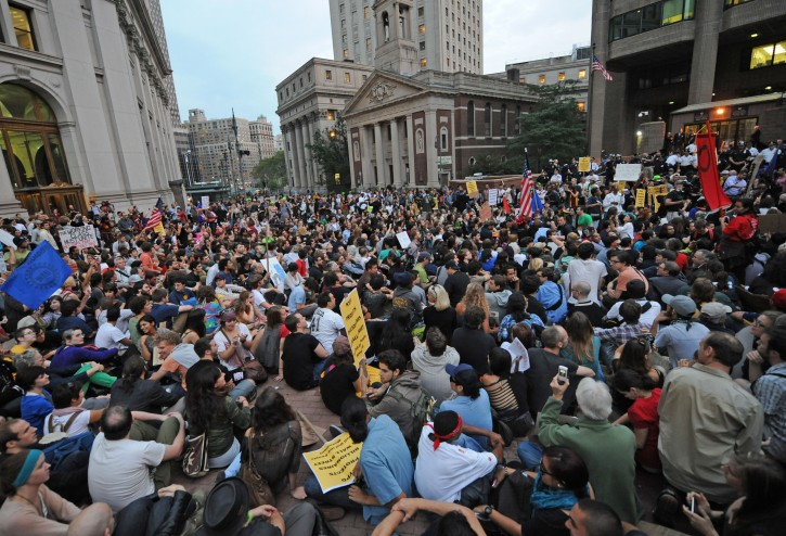 """Protestors sit in the plaza of Police Headquarters, Friday, Sept. 30, 2011, in New York.  The """"Occupy Wall Street"""" protest is in its second week, as demonstrators speak out against corporate greed and social inequality. (AP Photo/ Louis Lanzano)"""