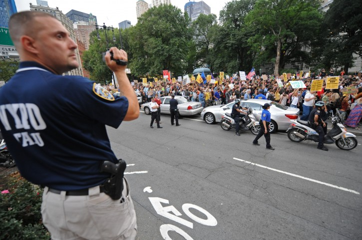 """An officer videotapes a several block long march up Broadway towards Police Headquarters, Friday, Sept. 30, 2011, in New York. The """"Occupy Wall Street"""" protest is in its second week, as demonstrators speak out against corporate greed and social inequality.  (AP Photo/ Louis Lanzano)"""