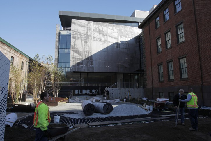 Workmen put the finishing touches on the grounds around Building 92 at the Brooklyn Navy Yard in New York, Wednesday, Nov. 2, 2011. The Brooklyn Navy Yard Center at Building 92, which explores the history and current uses of the Navy Yards, opens to the public on Friday, Nov. 11, 2011. (AP Photo/Seth Wenig)