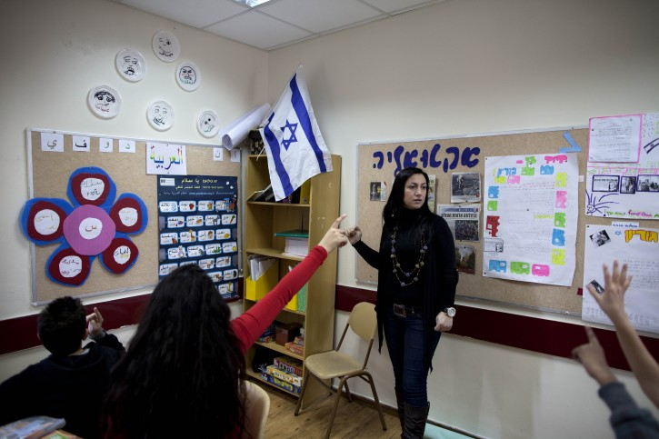Israeli Arab Maram Faour, a teacher from the Arab town of Kabul gives an Arabic class to Israeli schoolchildren in a school at the northern Israeli village of Yokneam, Tuesday, Dec 20, 2011. In an educational revolution of sorts, a growing number of Israeli schools are taking a novel approach to the instruction of Arabic They're hiring Arab teachers. The initiative is about far more than teaching children a new language. Educators say they hope to break down barriers in a society where Jewish and Arab citizens have little day-to-day interaction and often view each other with suspicion.(AP Photo/Oded Balilty)