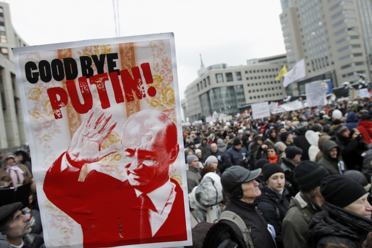 """Protesters carry a depiction of Putin bearing the words """"Good Bye Putin"""" as they gather to protest against alleged vote rigging in Russia's parliamentary elections on Sakharov avenue in Moscow,  Russia, Saturday, Dec. 24, 2011. Tens of thousands of demonstrators on Saturday cheered opposition leaders and jeered the Kremlin in the largest protest in the Russian capital so far against election fraud, signaling growing outrage over Prime Minister Vladimir Putin's 12-year rule. (AP Photo/Ivan Sekretarev)"""