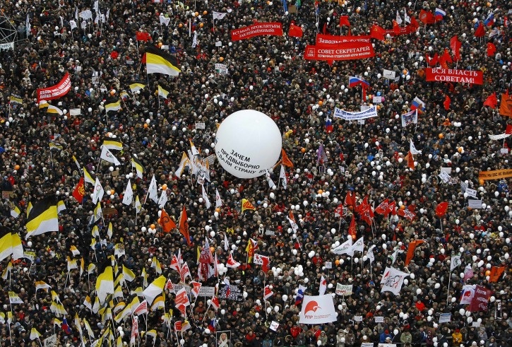 """Protesters gather together to protest against alleged vote rigging in Russia's parliamentary elections on Sakharov avenue in Moscow,  Russia, Saturday, Dec. 24, 2011, with a white balloon with words """"why did you join WTO?"""". Tens of thousands of demonstrators on Saturday cheered opposition leaders and jeered the Kremlin in the largest protest in the Russian capital so far against election fraud, signaling growing outrage over Prime Minister Vladimir Putin's 12-year rule. (AP Photo/Alexander Zemlianichenko)"""