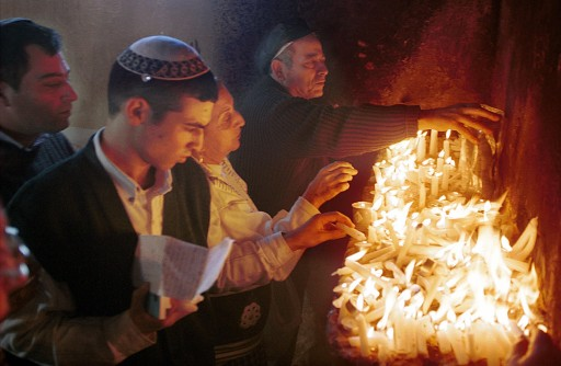 FILE - In this Tuesday, Dec. 28, 199 file photo, Jewish pilgrims light candles inside the shrine at the site of the 120 year-old tomb of Rabbi Abu Hatzeira northwest of Cairo, Egypt. (AP Photo/Enric Marti, File) EGYPT OUT