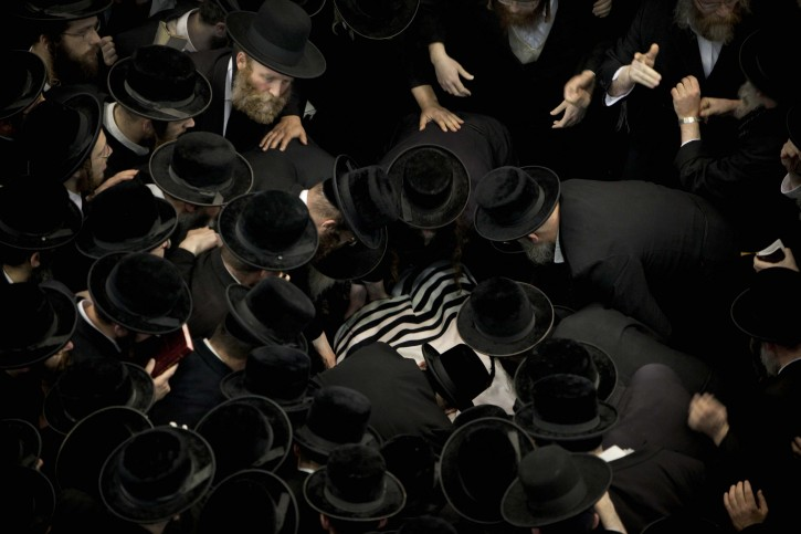Ultra Orthodox Jews gather around the  body of Rabbi Moshe Yehoshua Hager, leader of the Hassidic sect Vizhnitz in Israel,at the Vizhnitz Synagogue during his funeral procession in Bnei Brak , Ultra Orthodox Jewish town near Tel Aviv, Israel, Wednesday, March 14, 2012. Rabbi Moshe Yehoshua Hager was 95.(AP Photo/Oded Balilty)