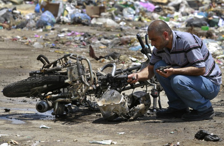 """A Palestinian inspects the debris of a destroyed motorcycle after an Israeli airstrike in Beit Hanoun, northern Gaza Strip, Monday, June 18 2012. Militants crossed from Egypt's turbulent Sinai Peninsula into southern Israel on Monday and opened fire on civilians building a border security fence, defense officials said. One of the Israeli workers was killed, and two assailants died in a gunbattle with Israeli troops responding to the attack. Several hours after the attack, an Israeli airstrike killed two men riding a motorcycle in the northern Gaza Strip near the Israeli border. The Islamic Jihad militant group said the men were members on a """"reconnaissance"""" mission and vowed revenge. (AP Photo/Hatem Moussa)"""