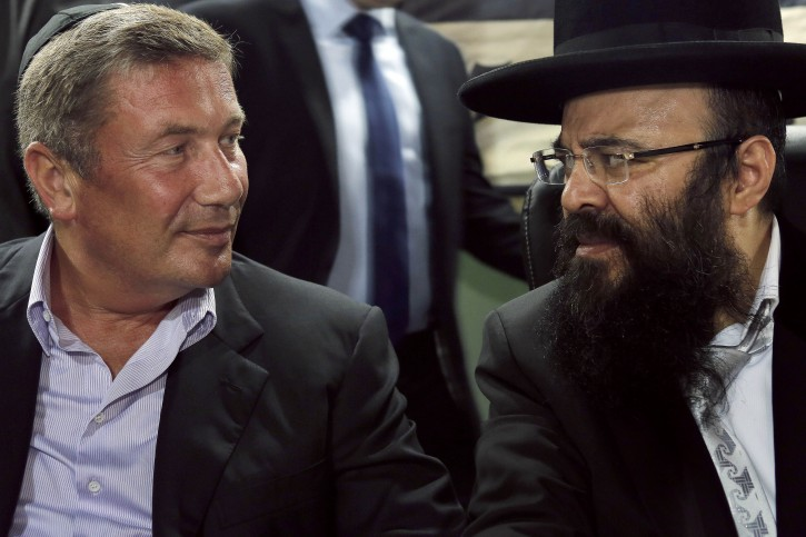 In a Sunday July 1, 2012 photo,  Rabbi Yaakov Israel Ifargan, right, known as the 'X-Ray' rabbi for the belief he has the ability to diagnose patients by eyesight only, sits next to businessman Nochi Dankner, left, at the annual gathering of the rabbi's followers and supporters in the town of  Netivot, southern Israel. Over the past few decades, Ifargan and dozens of other rabbis have carefully positioned themselves at the fulcrum of Israeli power and influence. (AP Photo/Tsafrir Abayov)