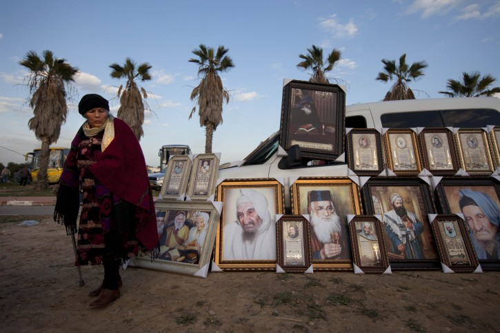 FILE -In a Thursday Jan. 26, 2012 file photo a Jewish woman stands next to pictures of rabbis for sale near the tomb of the Baba Sali, Rabbi Yisrael Abuhatzeira, during the annual pilgrimage to his grave on the 28th anniversary of his death, in the southern Israeli town of Netivot. Over the past few decades, dozens of rabbis have carefully positioned themselves at the fulcrum of Israeli power and influence. (AP Photo/Oded Balilty, File)