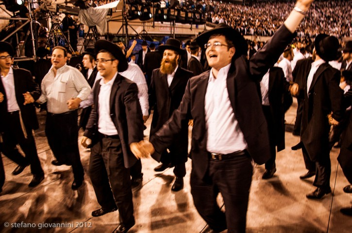 Orthodox Jews dance during the 12th Siyum HaShas, a celebration marking the completion of the Daf Yomi, a seven-and-a-half-year cycle of studying texts from the Talmud, the canon of Jewish religious law, at the MetLife Stadium in East Rutherford New Jersey August 1, 2012. Photo: Stefano Giovannini for VIN News