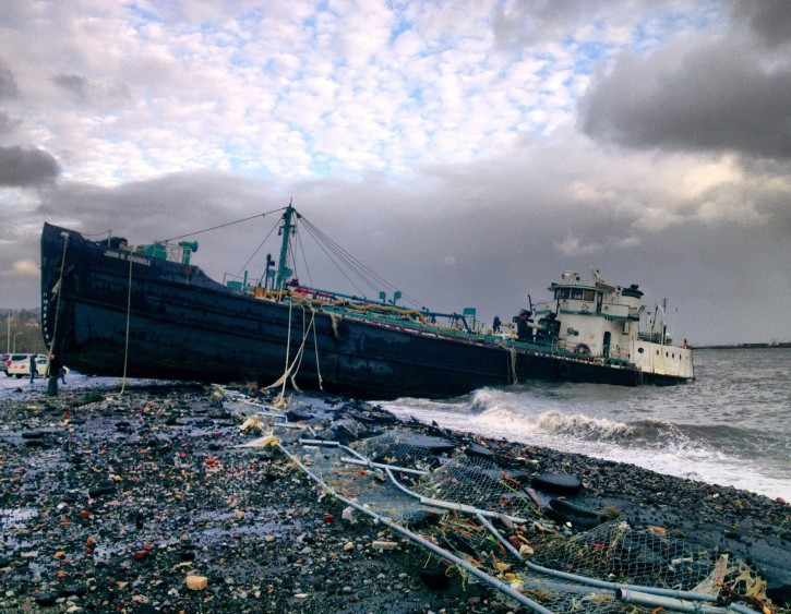 A 168-foot water tanker, the John B. Caddell, sits on the shore Tuesday morning, Oct. 30, 2012 where it ran aground on Front Street in the Stapleton neighborhood of New York's Staten Island as a result of superstorm Sandy. (AP Photo/Sean Sweeney)