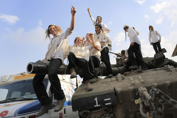 Ultra-Orthodox Jews of the Bratslav Hasidic sect, that gathered to show support for the forces, dance as they celebrate atop of a tank in southern Israel, close to the Israel Gaza Strip Border, Thursday, Nov. 22, 2012. (AP Photo/Tsafrir Abayov)