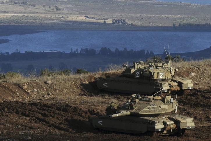 Israeli tanks sat in position overlooking a Syrian village Monday. (Avihu Shapira/Reuters)