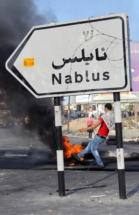 A Palestinian demonstrator lights a tire during clashes in a protest against Israel's operations in the Gaza Strip, at Huwwara checkpoint near Nablus, the West Bank, 21 November 2012. According to Palestinian sources, 24 Palestinians were injured during the clashes. EPA/ALAA BADARNEH