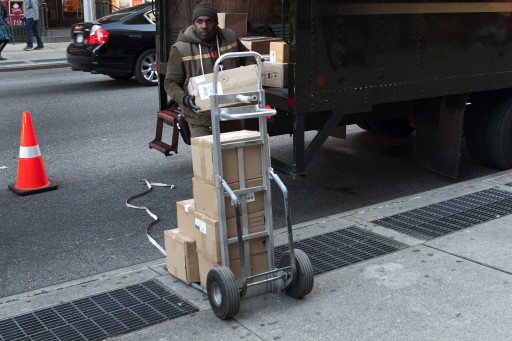 A UPS delivery man unloads boxes from a truck in New York November 26, 2012. REUTERS/Keith Bedford