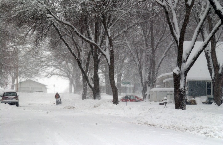 Falling snow and high winds create poor visibility for a Wilmar, Minn. resident using a snowblower, Sunday, Dec. 9, 2012 during the first major snow storm of the season. (AP Photo/The West Central Tribune, Ron Adams)