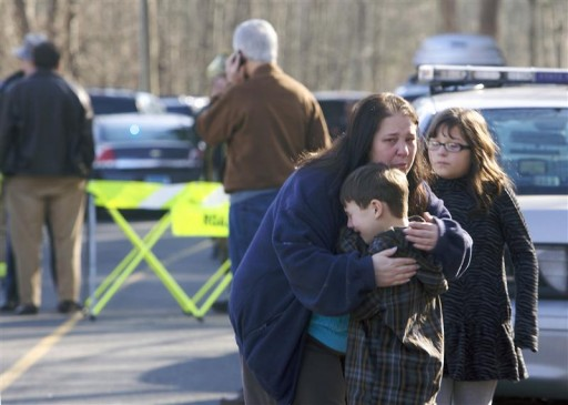 A young boy is comforted outside Sandy Hook Elementary School after a shooting in Newtown, Connecticut, December 14, 2012. Reuters