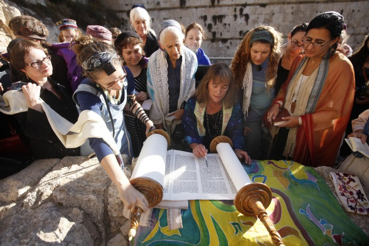Religious Jewish women, which are part of the Women of the Wall organization, wear prayer shawls and tallit as they hold the Torah and pray near the Western Wall in Jerusalem. EPA/MIRIAM ALSTER